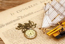 Ship Made Of Wood And Fabric Handmade And Vintage Watches On The Background Of An Excerpt From A Copy Of The Document Of 1776 On The Signing Of The Independence Of America