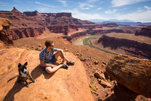 A Man Sits With A Puppy While Looking Out Over A Bend In The Colorado River From A Viewpoint At The End Of The Short 0.3 Mile Gooseneck Trail In Canyonlands National Park, Utah. The La Sal Mountains Are In The Distance.