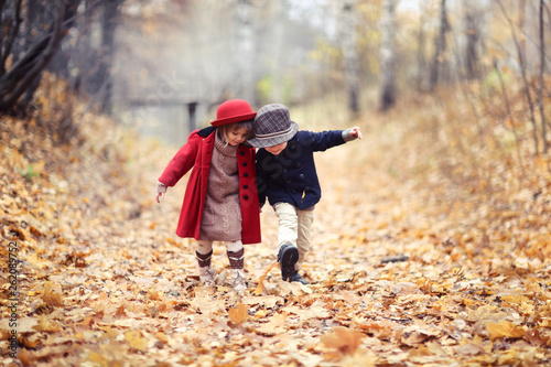 Obraz boy and girl in hats walk in park, autumn mood - fototapety do salonu