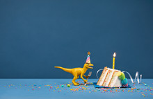 Yellow Dinosaur Eating Birthday Cake Slice Over Blue Background