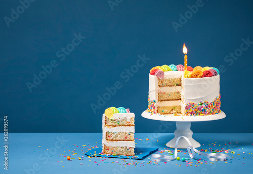 Fotografia Colorful Birthday Cake with Slice and Sprinkles on Blue