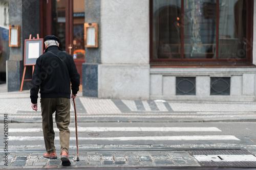 Fényképezés An elderly male with a walking stick slowly walks across a crosswalk in the midd