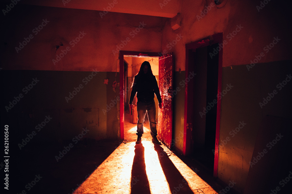 Fototapeta Creepy silhouette with knife in the dark red illuminated abandoned building. Horror about maniac concept