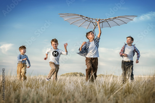 Stampa su Tela Boys with a kite in the field