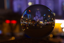 Lens Ball Photo Of Palace Of Culture And Science Warsaw - Reflection In Crystal Ball At Night In Rainy Autumn Time.