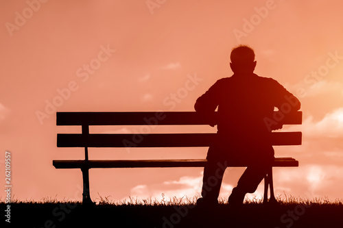 Obraz old man sitting alone on park bench under tree; - fototapety do salonu