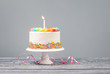 Leinwanddruck Bild - White Birthday Cake with one Candle and Colorful Icing