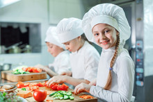 Children Grind Vegetables In The Kitchen.
