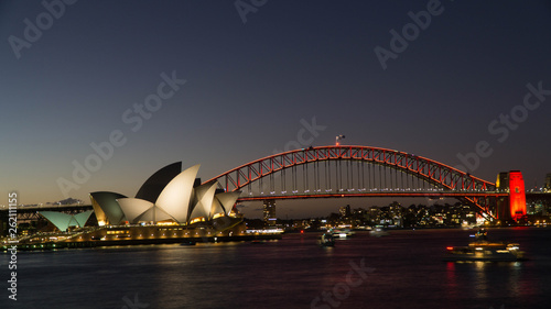 Poster Australie A Night view of the famous Sydney Opera House and the Harbour Bridge seen from Royal Botanical gardens, Australia