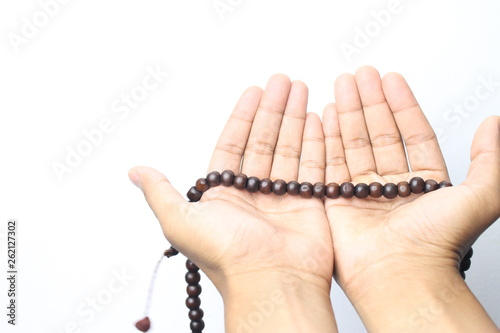 Photo  Male hand holding muslim beads rosery or tasbih over white background