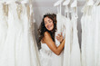 canvas print picture - Beautiful young brunette woman choosing wedding dress in a bridal salon.