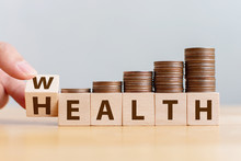 Hand Flip Wooden Cube With Word Wealth To Health With Coins Stack Step Up Growing Growth Value. Investment In Life Insurance And Healthcare Concept