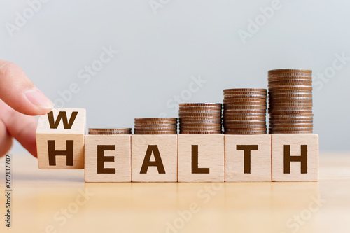 Hand flip wooden cube with word wealth to health with coins stack step up growing growth value Fototapet