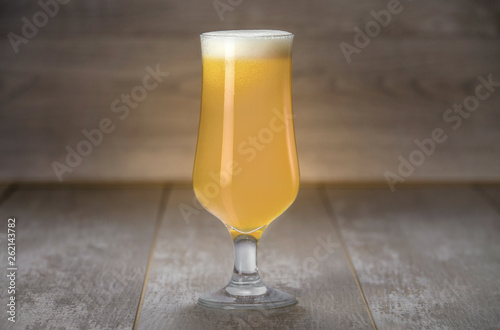 Photo  A delicious New England IPA beer in a craft brewery tulip glass, on wooden backg