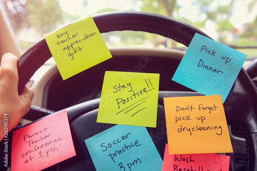 Photo  Steering wheel covered in notes as a reminder of errands to do