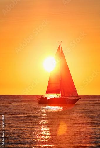 Obraz na plátně Sailing yacht at sunset, sun setting behind the sail