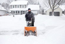 Man Using A Snowblower To Clea...