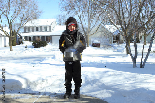 Fotografering  Boy ready to throw a pan of boiling water that will freeze into ice crystals on