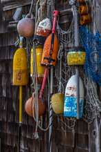 Bright And Colorful Lobster Floats And Lobster Buoys Hanging On Wood Shingled Wall