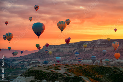 Foto auf AluDibond Rotglühen Hot Air balloons flying tour over Mountains landscape spring sunrice Cappadocia, Goreme Open Air Museum National Park, Turkey nature background.