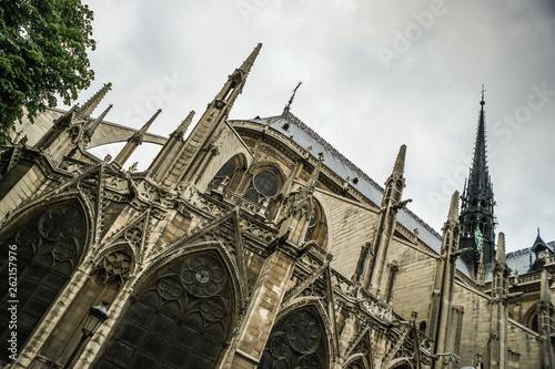 Fotografia  The Notre Dame De Paris- Our Lady of Paris  cathedral,  against cloudy sky