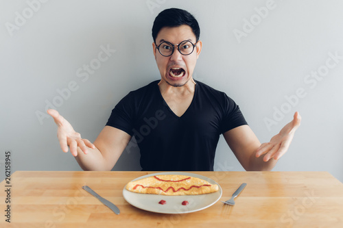 Valokuvatapetti Angry and mad face of man is eating homemade breakfast set of omelet