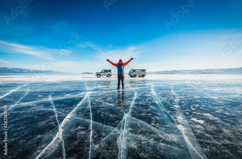 Photo Traveler man wear red clothes and raising arm standing on natural breaking ice in frozen water at Lake Baikal, Siberia, Russia