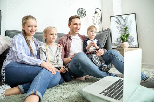 Valokuva  Happy family watching cartoons at home