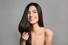 Portrait Of Beautiful Young Woman With Healthy Long Hair On Grey Background