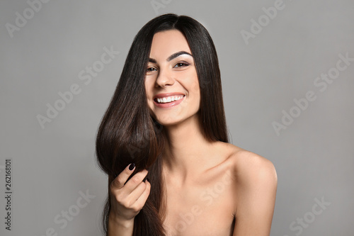 Foto Portrait of beautiful young woman with healthy long hair on grey background