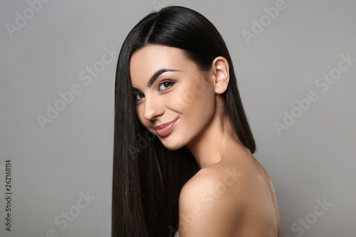 Leinwand Poster Portrait of beautiful young woman with healthy long hair on grey background