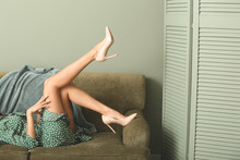 Young Woman In Elegant High Heels Lying On Sofa In Room