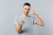 canvas print picture - Young man in casual clothes doing phone gesture like says call me back, pointing index finger on camera isolated on grey wall background. People sincere emotions lifestyle concept. Mock up copy space.