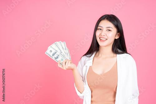 Fotografia  Successful beautiful Asian business young woman holding money US dollar bills in