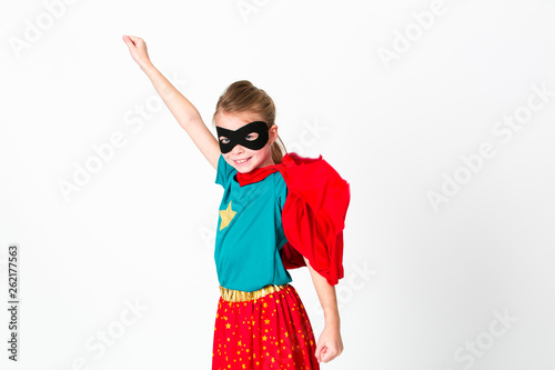 blond supergirl with black mask and red cape posing in front of white background Tableau sur Toile