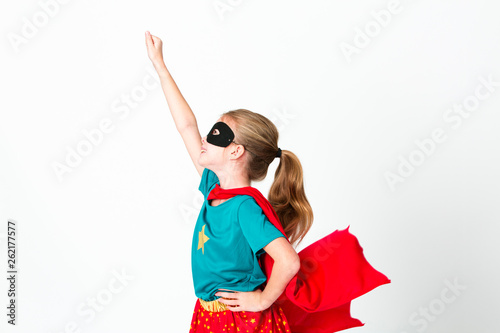Photographie blond supergirl with black mask and red cape posing in front of white background