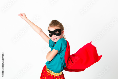 blond supergirl with black mask and red cape posing in front of white background Canvas Print