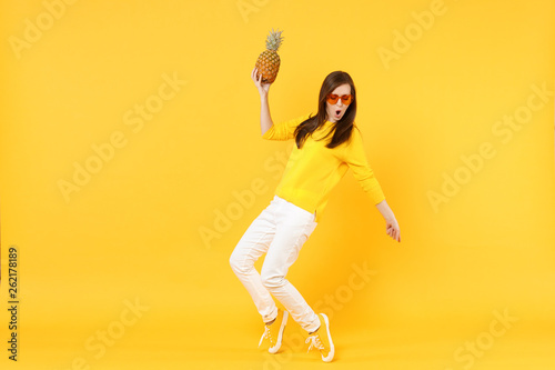 Poster Dance School Funny young woman in heart glasses dancing, holding fresh ripe pineapple fruit isolated on yellow orange wall background in studio. People vivid lifestyle, relax vacation concept. Mock up copy space.