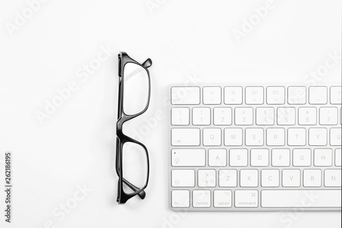 Canvastavla  reading glasses and computer keyboard isolated on white background with copy spa