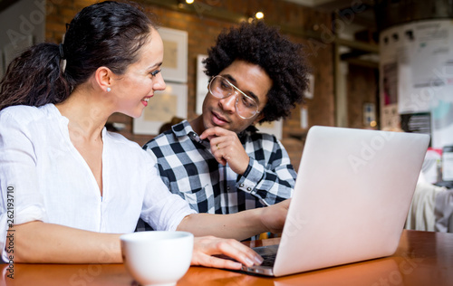 Multiethnic people meeting at cafe, advisor showing offer to client on laptop Canvas Print