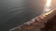 Aerial View Golden Sunset Over The Sea With Waves Crashing On The Shore With Beautiful Reflections On The Water And Far Away, One Alone Fisherman, Performs Surf Casting Discipline