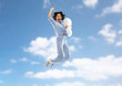 canvas print picture fun, people and bedtime concept - happy young woman full of energy in blue pajama holding pillow and jumping over blue sky and clouds background