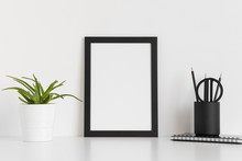 Black Frame Mockup With A Succulent Plant And Workspace Accessories On A White Table. Portrait Orientation.