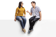 Young Man Sitting On A Blank Signboard And Talking To A Young Woman