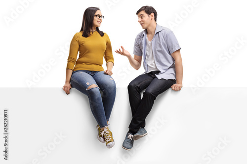 Young man sitting on a blank signboard and talking to a young woman Canvas Print