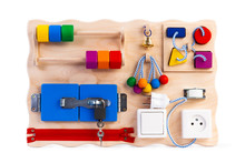Educational Toy For Children, Babies On A White Isolated Background, Consisting Of A Sorter, A Zipper For Clothes,  Switch, Beads, A Labyrinth, A Lock With A Key, Roller, Bell, Rosette