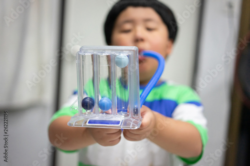 Photo A boy is testing and administering lungs with a tri-ball dryer.