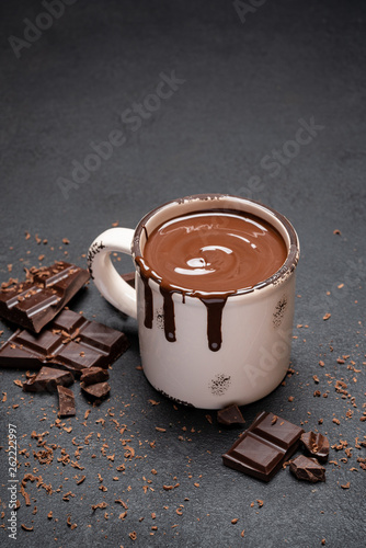 Fotografia Cup of hot chocolate and pieces of chocolat on dark concrete background