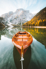 Fototapeta Optyczne powiększenie Traditional rowing boat at Lago di Braies at sunrise in fall, South Tyrol, Italy