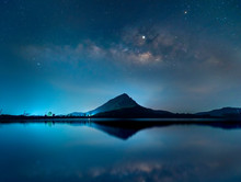 Night Sky With Stars And The Milky Way Is Above The Mountain And Reflection On The Water (Lam Isu Reservoir) Kanchanaburi, Thailand